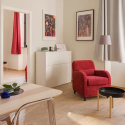 red armchair and coffee table in a clean, bright, well ventilated living room